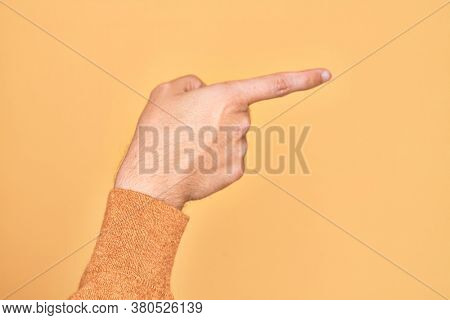 Hand of caucasian young man showing fingers over isolated yellow background pointing with index finger to the side, suggesting and selecting a choice