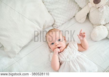 Cute Little Baby Girl With Blue Eyes 4 Months Lying On Bed, Finger In Mouth. Small Cute Funny Baby I