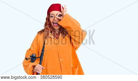 Young latin woman wearing fisher raicoat holding rod smiling happy doing ok sign with hand on eye looking through fingers