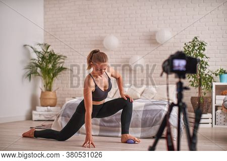Athletic Woman Blogger In Sportswear Shoots Video On Camera As She Does Exercises At Home In Living