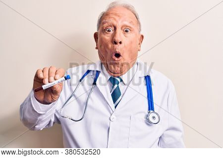 Senior handsome grey-haired doctor man holding coronavirus test tube with blood sample scared and amazed with open mouth for surprise, disbelief face