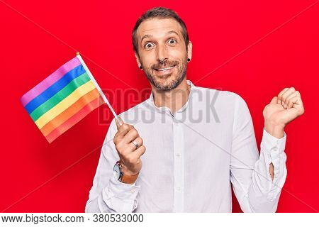 Young handsome man holding rainbow lgbtq flag screaming proud, celebrating victory and success very excited with raised arm