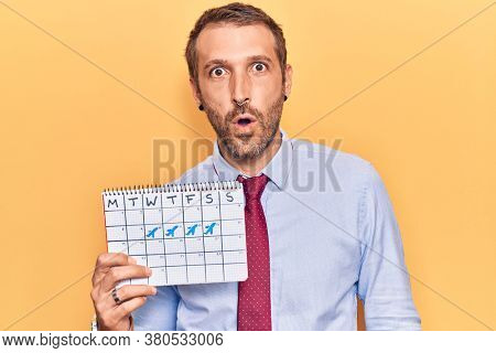 Young handsome man holding travel calendar scared and amazed with open mouth for surprise, disbelief face
