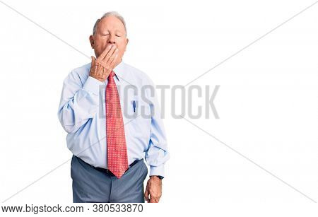 Senior handsome grey-haired man wearing elegant tie and shirt bored yawning tired covering mouth with hand. restless and sleepiness.