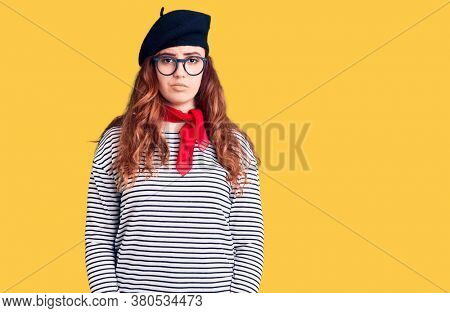 Young beautiful woman wearing french look with beret with serious expression on face. simple and natural looking at the camera.