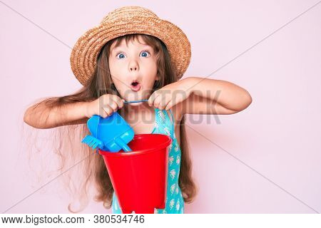 Little caucasian kid girl with long hair playing with summer shovel and bucket toys scared and amazed with open mouth for surprise, disbelief face