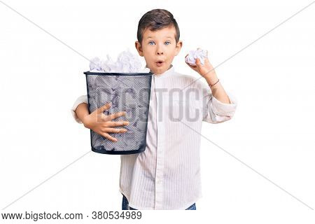 Cute blond kid holding paper bin full of crumpled papers scared and amazed with open mouth for surprise, disbelief face