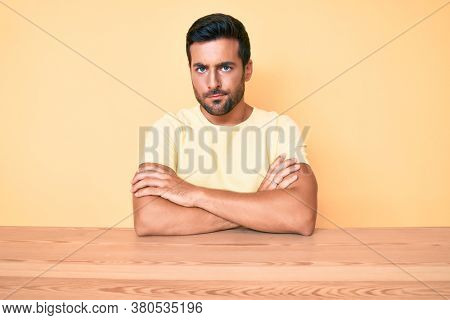 Young hispanic man wearing casual clothes sitting on the table skeptic and nervous, disapproving expression on face with crossed arms. negative person.