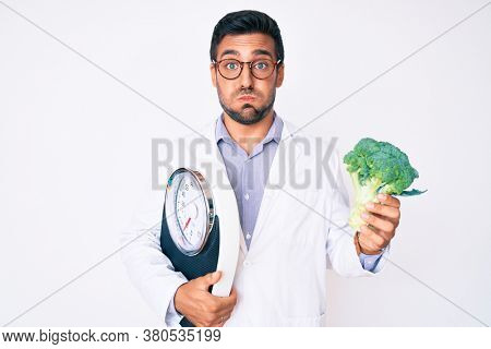 Young hispanic man as nutritionist doctor holding weighing machine and broccoli puffing cheeks with funny face. mouth inflated with air, catching air.