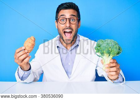 Young hispanic man as nutritionist doctor holding croissant and broccoli celebrating crazy and amazed for success with open eyes screaming excited.
