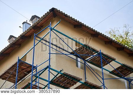 Scaffolding On Construction Site. Incomplete Building And Decoration With Scaffolds. Work In Progres