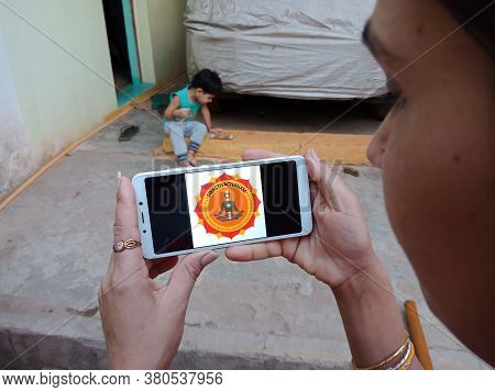 District Katni, India - 28 May 2020: An Indian Lady Holding Smart Phone With Displaying Swasti Vacha