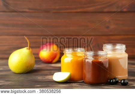 Glass Jars With Nutrient Baby Food And Fruit On Brown Background. Vegetable And Fruit Puree