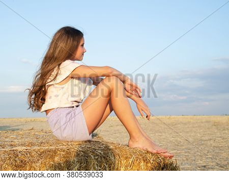 Adorable Little Girl Child Sitting On A Hay Rolls In A Wheat Field At Sunset