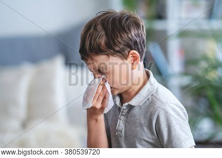 Sick Boy Blowing Nose Into Tissue, Unhealthy Child Suffering From Running Nose Or Sneezing And Cover