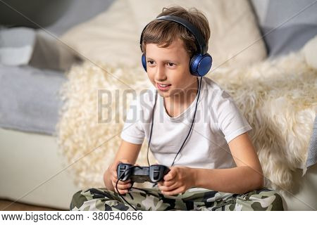 Cheerful Boy In Headphones, With Joystick In His Hands, Playing Video Games. Child Has Fun Activitie