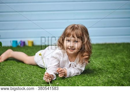 Cute Little Girl, In A White Dress With Wavy Hair, Is Lying On A Green Rug Made Of Artificial Grass.