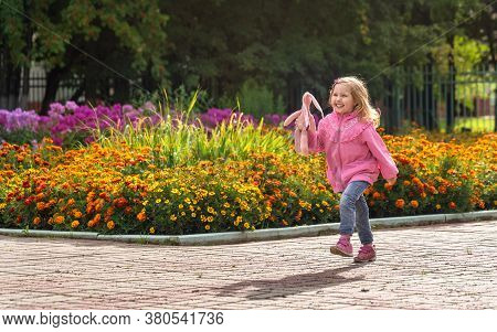 Happy Girl Dressed In Denim Pants And A Light Jacket And Sports Shoes Runs Through The Park And Laug