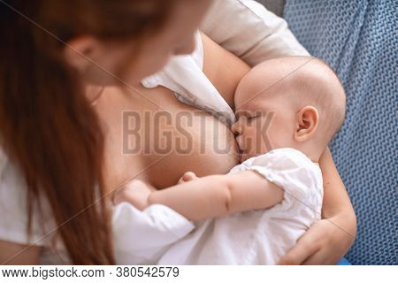 Process Of Breastfeeding. A Mother Breast-feeds Her Child. The Baby Sucks Its Mother's Breast Milk A