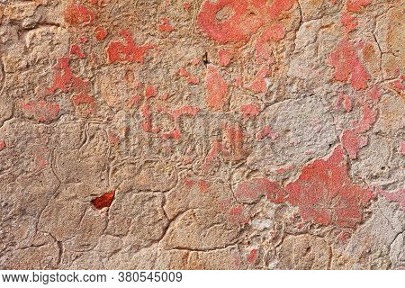 Old Wall With Scratched Plaster And Remains Of Pink Paint - Grunge Background Texture
