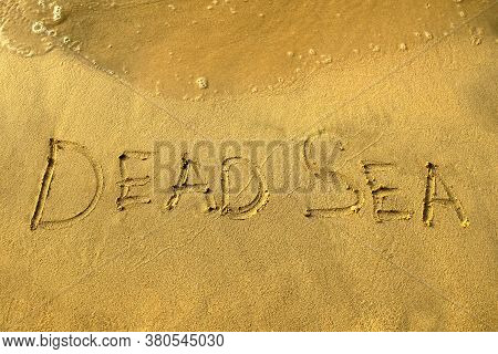 Dead Sea Words On Beach Sand. Dead Sea Phrase Is Written On A Sand With Water Waves.