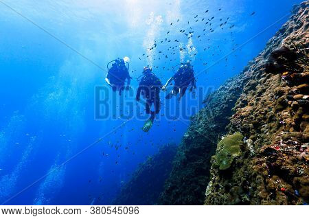 Underwater Photo Of Scuba Divers In The Blue. From A Scuba Dive At The Reefs Of Koh Haa In Thailand.