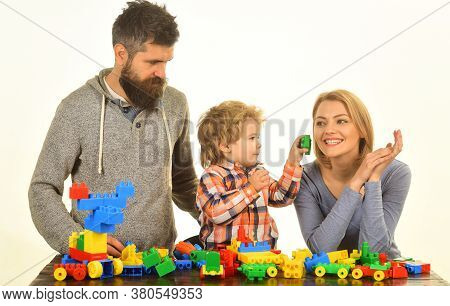 Parents And Kid In Playroom. Man, Woman And Boy