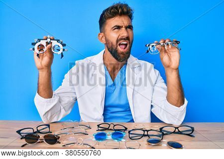Young hispanic man with optometry glasses sitting at the table angry and mad screaming frustrated and furious, shouting with anger. rage and aggressive concept.