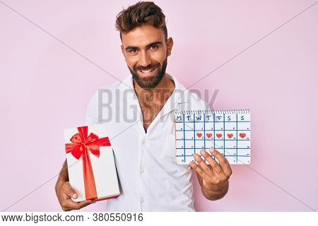 Young hispanic man holding heart calendar and paper airplane scared and amazed with open mouth for surprise, disbelief face