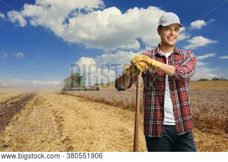 Male farmer standing on a wheat field with a combine harvester in the back