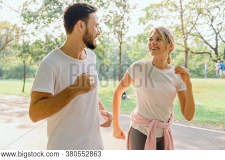Young Sweet Couple Talk During Active Run In The Park. The Lover Doing Sports Exercises In The Morni