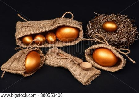 Eggs In Golden Color In Burlap Bags, Nest And Spoon