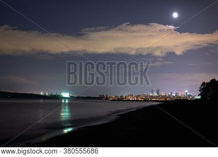 English Bay Night Vancouver Moon. The moon rising over the Vancouver skyline on English Bay. British Columbia, Canada.