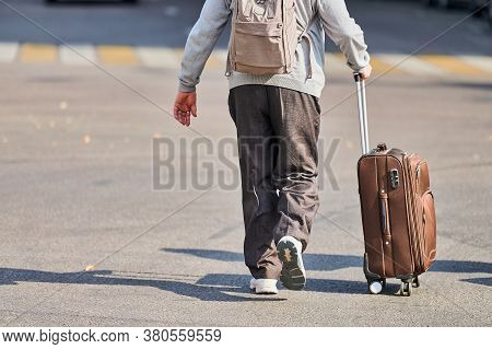Old Man With Suitcase On Wheels. Male With Luggage Bag Walking Down The Street From Airport. Homecom