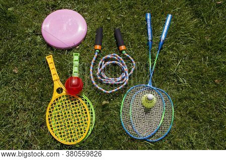 Group Of Sports Equipment Including Tennis Rackets, Badminton Rackets, Skipping Rope And Frisbee On