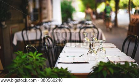 Empty Restaurant Tables Outdoors. Wineglasses, Napkins And Cutlery Prepared For Celebration Party. L