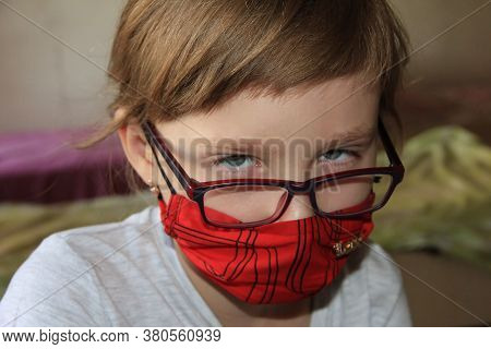 A Girl In A Red Mask And Glasses. A Hurt Child