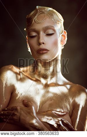 Beauty portrait of young attractive fashion model with short wet blond hair. Golden paint on body. Blue eyes, professional makeup. Warm colors. Natural sunlight and shadows on background indoors.