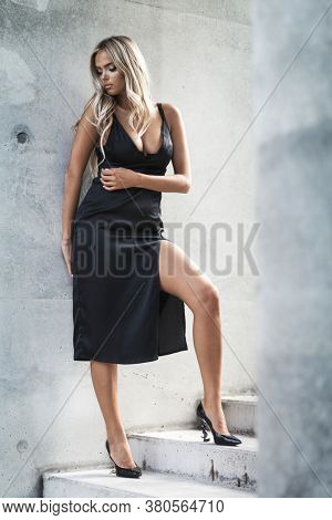 Portrait of blond young woman with beautiful makeup and hair in a classic black dress standing near grey wall. Fashion model posing in elegant clothes outdoors in urban enviroment. Natural sunlight.
