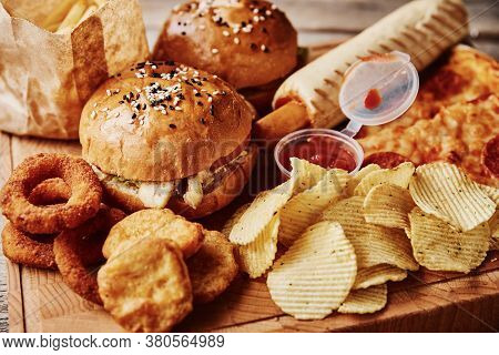 Unhealthy Products And Junk Food. Different Types Of Fastfood And Snacks On The Table, Close Up. Tak