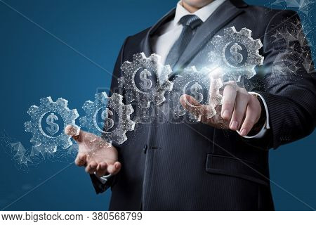 Businessman Clicks On A Hologram Of Gears With Dollar Signs On A Blue Background.