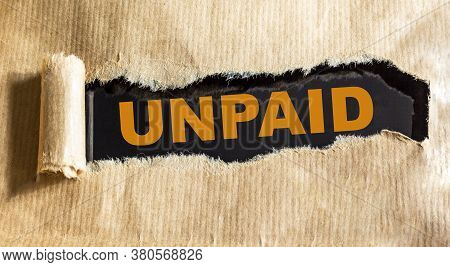 Unpaid. Text On Torn Brown Paper And Black Background.