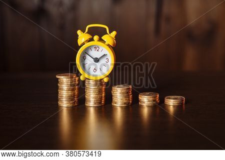 Business Financial Ideas Concept With Coins Stack And Yellow Alarmclock On Wooden Background