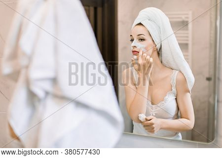 Smiling Beautiful Lady With White Towel On Her Head, Applying Skincare Mud Mask On Face Looking In B