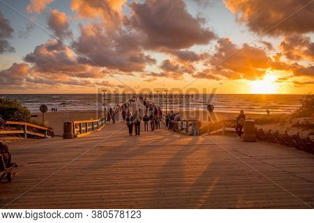 Palanga, Lithuania - July 12, 2020: Tourists Are Watching A Sunset At A Famous Marine Palanga Pier O