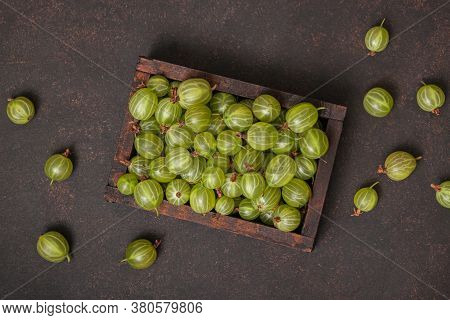 Ripe Green Gooseberry Berry In Wooden Box. Green Gooseberry On Brown Background. Top View