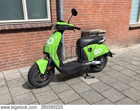 Groningen, The Netherland - July 26, 2020: Green Electric Go Sharing Scooter Parked By The Side Of T