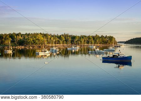 Sunset On A Cove In Pretty Marsh In Maine.  Several Boats Sit Anchoored In The Water With The Sun Ca