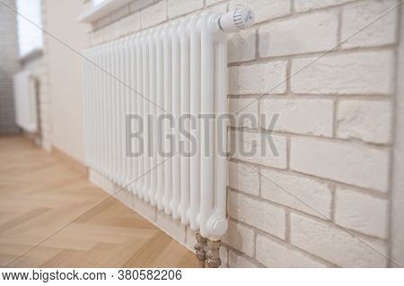 Radiator And Thermostat In The Apartment - Heater Close-up. Apartment Interior - Radiator On A White