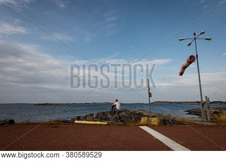 a young lone man sits on a rock waiting for a late ferry. travel through the harsh Scandinavian Isla